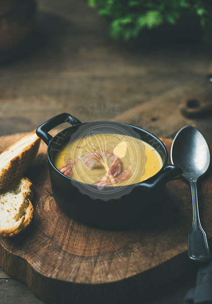 Corn creamy soup with shrimps served in individual pot with bread on board over rustic dinner table