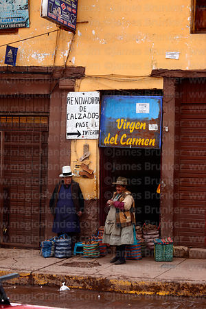 Quechua women with bags of potatos outside shoe repair shop, Cusco, Peru