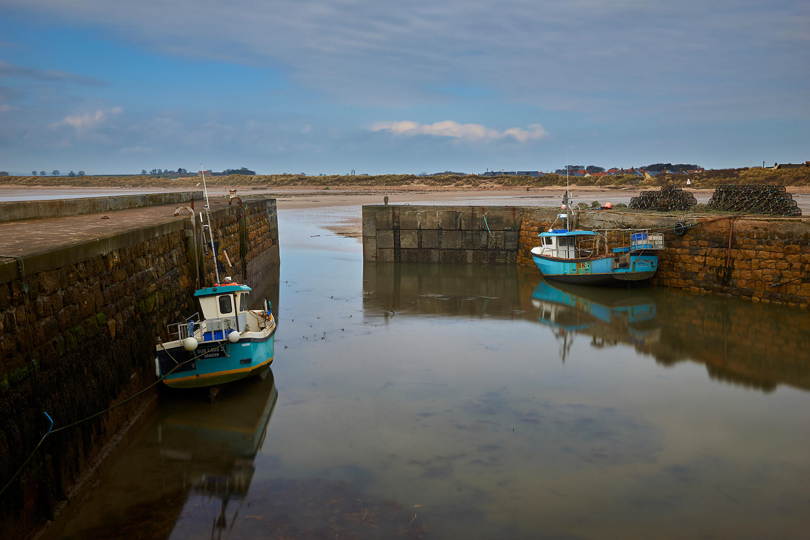 Fishing boats in a harbour at low tide