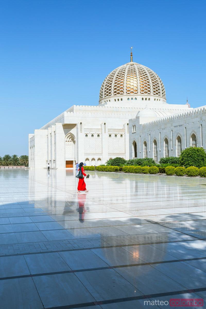 Oman, Muscat. Woman walking outside Sultan Qaboos Grand Mosque