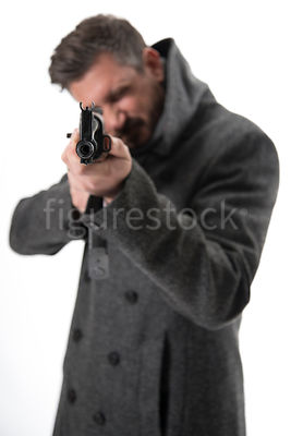 A blurred mystery man in a big coat, pointing an AK-47 – shot from eye level.