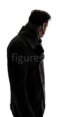 A semi-silhouette of a mystery man in a big coat, looking away – shot from eye level.