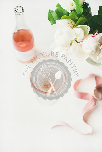 Rose wine in glass, pink ribbon, peony flowers, copy space