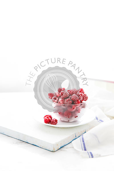 Raspberries in a clear bowl on a white background