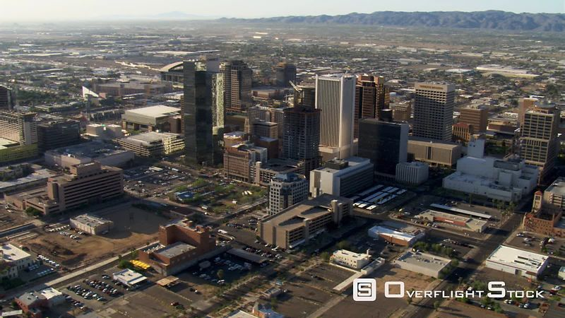 Flight past downtown Phoenix with wide view to mountains.