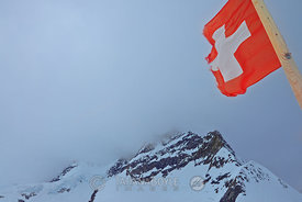 Mt Jungfrau in clouds and Swiss flag; Jungfraujoch, Valais - Bern, Switzerland