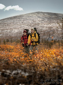 Two women hiking in autumn landscape