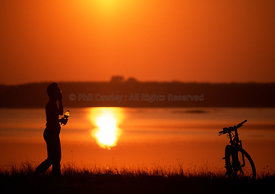 silhouette of cyclist taking a break with a bottle of water sunset