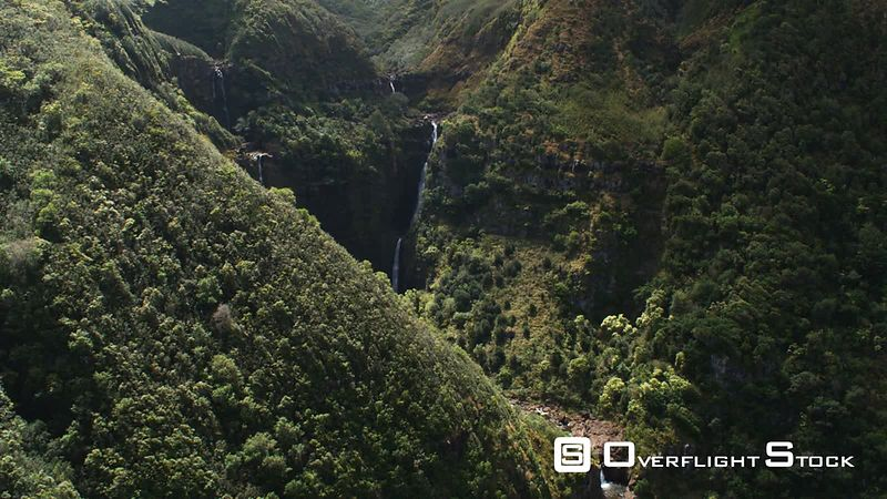 Flight past steep wooded slope to reveal and orbit plunging waterfalls on Molokai.