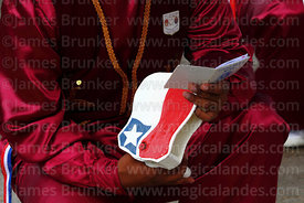 Morenos dancer holding rattle and song / prayer book at St Peter and St Paul festival, Arica, Chile