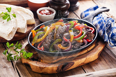 Beef Fajitas with colorful bell peppers in pan and tortilla bread and sauces