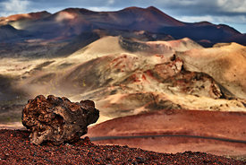 An ancient volcanic rock against the volcanoes in Timanfaya national park, Lanzarote