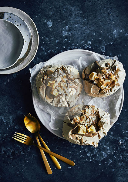 Caramel and toasted coconut meringues with dehydrated pinapple on top. on stand with newspaper