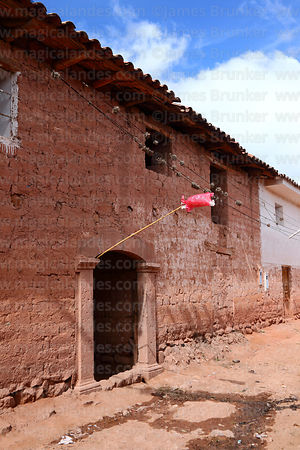 Red plastic bag on pole signifying a building that serves chicha (chichería), Maras, Cusco Region, Peru