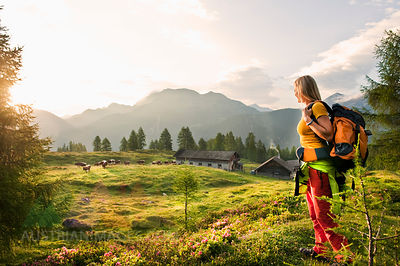 Austria, Salzburg County, Young woman standing in alpine meadow and watching landscape