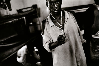 Rwanda - Gitarama - A young man accused of genocide crimes with a crucifi