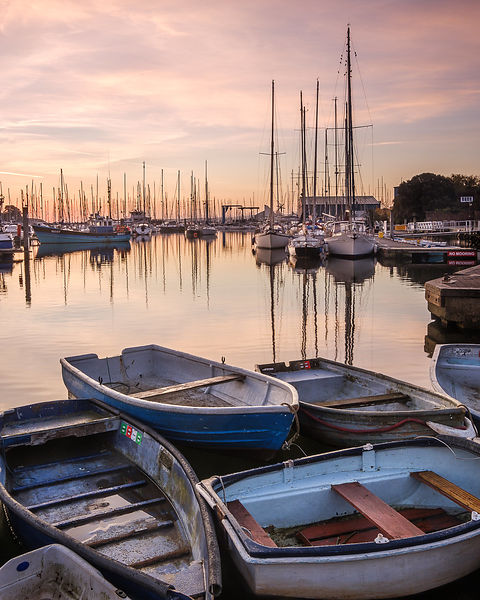 Early morning light upon the tenders, yachts and fishing boats at the Quay, Lymington, Hampshire, UK.