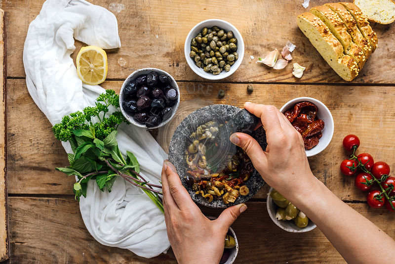 A woman mashing olives in a marble mortar to make olive tapenade is photographed from top view. Three types of olives, capers, sun-dried tomatoes herbs, corn bread slices accompany it.