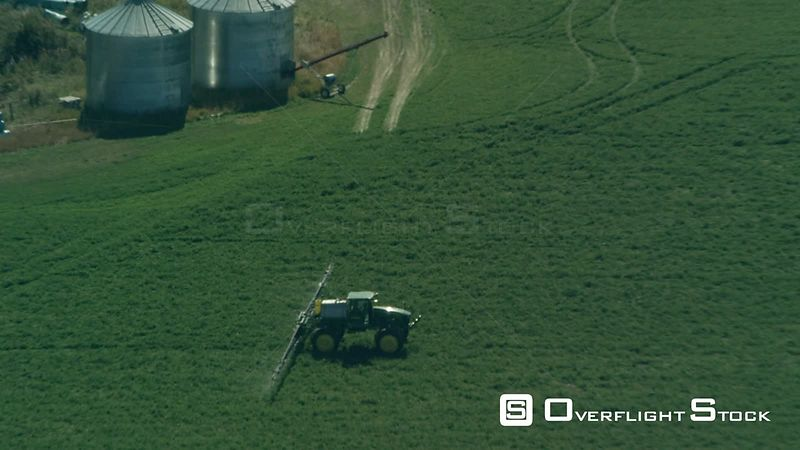 A Green John Deer tractor sprays chemicals on an alfalfa field near Bozeman, Montana