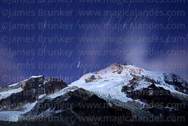 Star trails above Mt Huayna Potosí and lights of climbers ascending the peak on glacier, Cordillera Real, Bolivia