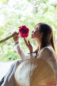 Vietnamese girl with traditional dress smelling red flowers
