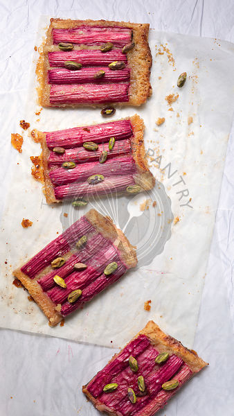 A rectangular rhubarb tart sprinkled with pistachio nuts and cut into pieces.