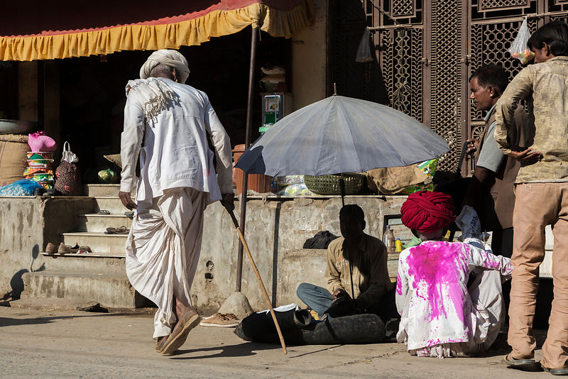 A Rabari Walks Past a Shoe Repair Man in the Street