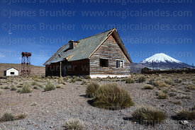 Abandoned timber house, Parinacota volcano in background, Caquena, Region XV, Chile