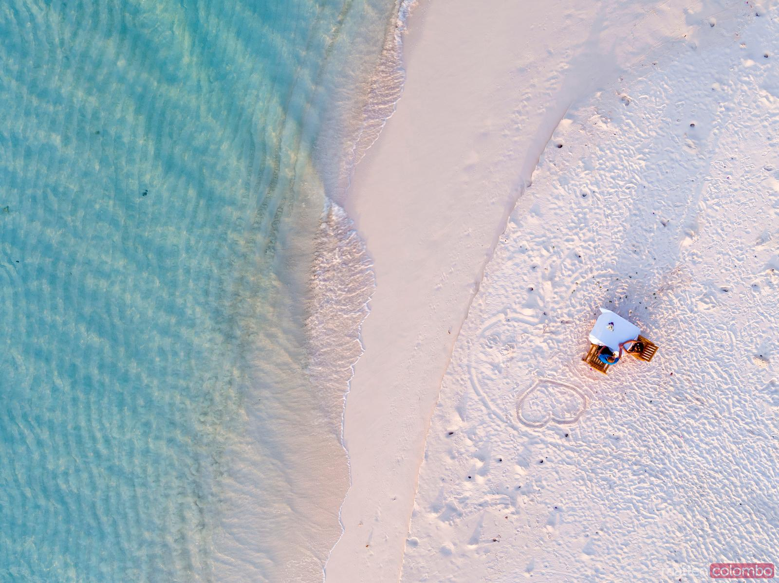 Overhead view of couple eating dinner on the beach