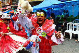 A pepino wearing beer glass glasses and holding his mask dancing during parades for the Entierro del Pepino, La Paz, Bolivia