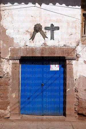 Black cross and rosette above doorway showing a family member has recently died, Maras, Cusco Region, Peru