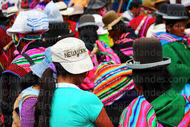 Teenage girl wearing New York baseball cap in middle of women wearing traditional bowler hats at festival in Caquiaviri, Bolivia