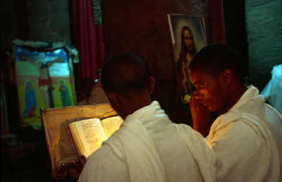 Ethiopia - Lalibela - Two Othodox Christian monks read a Bible by candlelight