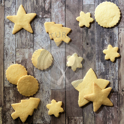A variety of homemade Christmas shortbread cookies on a wooden background.