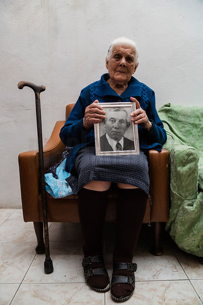 103 Year Old Maria Sulas with a Portrait of her Deceased Husband