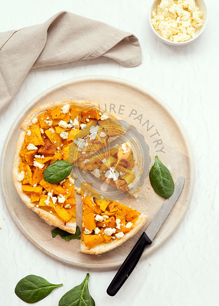 A round roasted pumpkin and feta cheese tart with cut pieces on a wooden serving board.
