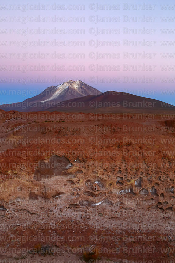 Eroded volcanic lava flow and Cerro Ollagüe volcano before dawn, Nor Lípez Province, Bolivia