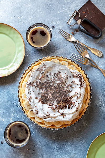 Banana cream pie decorated with chocolate curls and 2 cups of coffee on the table.