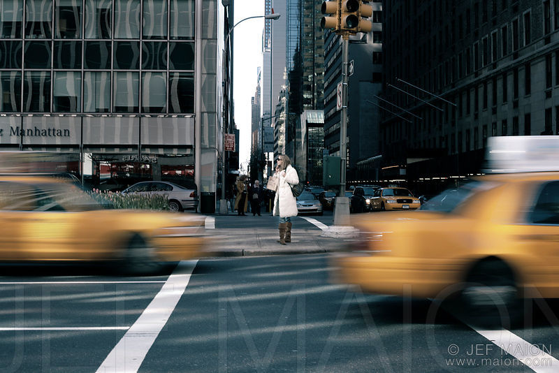 Woman standing on street with taxis passing by