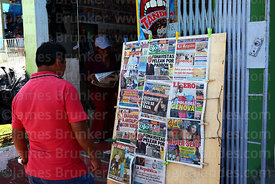 Man reading tabloid newspapers outside shop, Ilo, Peru