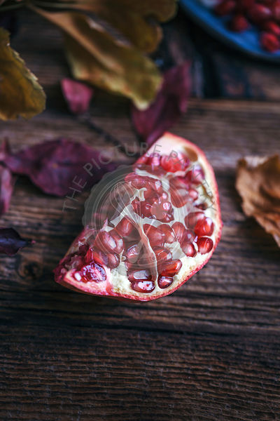 Piece of pomegranate on a rustic wooden table