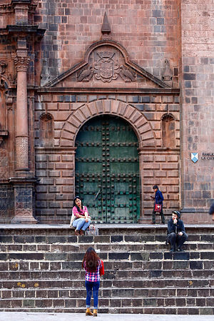 Girl taking photo of her friend with camera phone in front of right entrance of cathedral, Cusco, Peru
