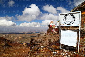 Club Andino Boliviano badge on litter bin, old ski hut in background, Mt Chacaltaya, Bolivia