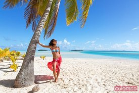 Woman leaning against palm tree, One Foot Island, Cook islands