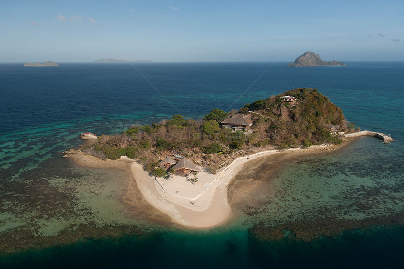 Aerial view of a private tropical island surrounded by a white sandy beach and coral reefs. note helipad at end of pier at top left of the island, Palawan, Philippines, April 2010