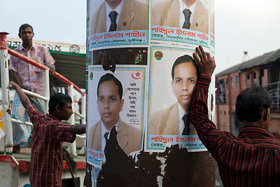 Bangladesh - Dhaka - A man waits by the quay for a ferry to dock and leans on political posters