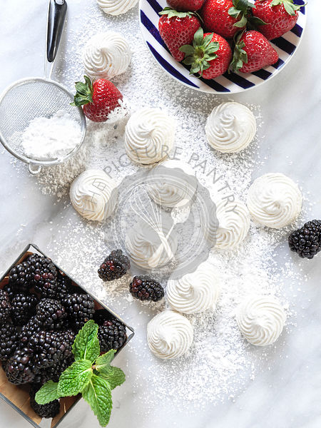 An array of red, white and blue desserts including strawberries, meringues, and blackmerries all on a marble surface.