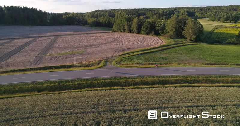 Man biking on the countryside, C4K aerial tracking view following a biker driving on a road, between wheat fields, on a sunny summer evening sunset, in Uusimaa, Finland