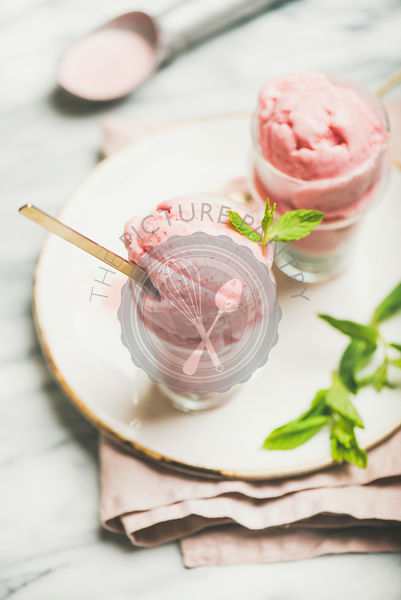 Homemade strawberry yogurt ice cream with mint on plate, vertical composition