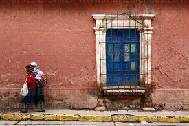 Indigenous woman carrying baby on her back walking past colonial house, Lampa, Peru